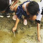 Three children test the waters of a mud puddle for mosquito larvae and pupae