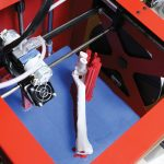 A bright red 3D printing machine is shown rendering a canine limb model.