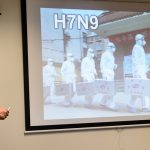 Professor Kawaoka stands in front of screen during a slide presentation on influenza strains.