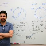 Professor Mostafa Zamanian stands in front of wipe board with drawings of parasite cycles.