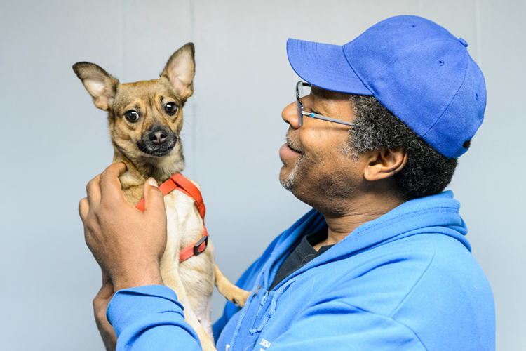 Man in blue baseball cap adoringly holds his little dog