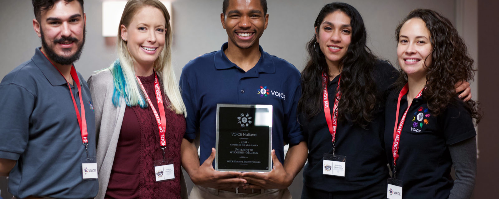 Officers of the UW SVM chapter of Veterinarians as One Inclusive Community for Empowerment (VOICE) accept the 2018-19 VOICE National Chapter of the Year Award. From left to right: Kameron Montana DVMx'20, Makenzi Travis-Balac DVMx'20, Kyle Granger DVMx'20, Priscilla Marroquin DVMx'21 and Jessica Carag DVMx'20. Not pictured: Melissa Sheth DVMx'21 and Clara Cole DVMx'21