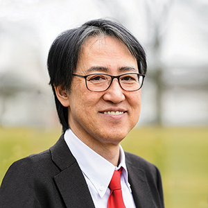 Man with glasses wearing a suit with a red tie.