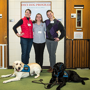 3 young veterinarian students pose with two service dogs